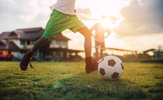 De actiesport van het silhouet in openlucht van een groep jonge geitjes die voetbalvoetbal spelen. Premium Foto