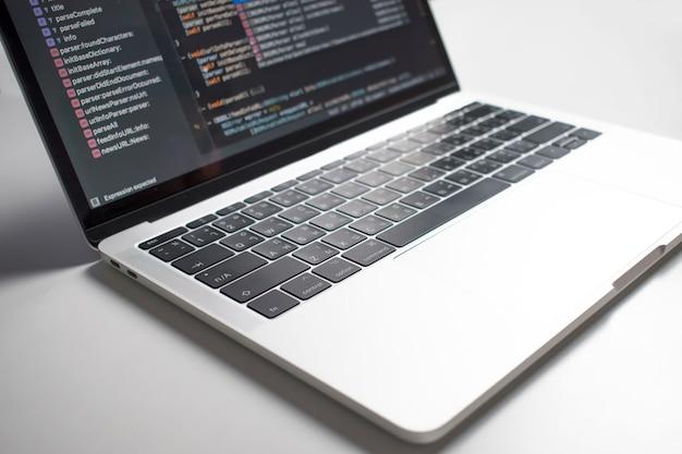 De afbeelding laat zien dat de codeontwikkelaars een computerscherm op een witte tafel hebben gemaakt. Premium Foto