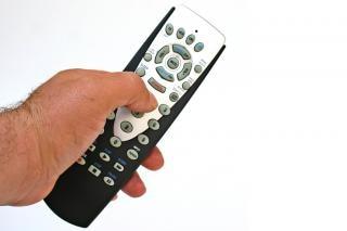 De afstandsbediening in de hand geïsoleerde Gratis Foto