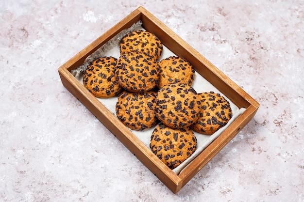 De amerikaanse koekjes van de stijlchocoladeschilfer in houten dienblad op lichte concrete achtergrond. Gratis Foto