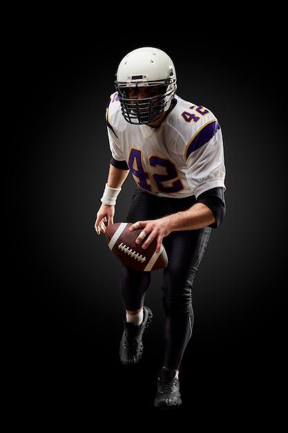 De amerikaanse speler van de voetbalsportman op zwarte. sport . Premium Foto
