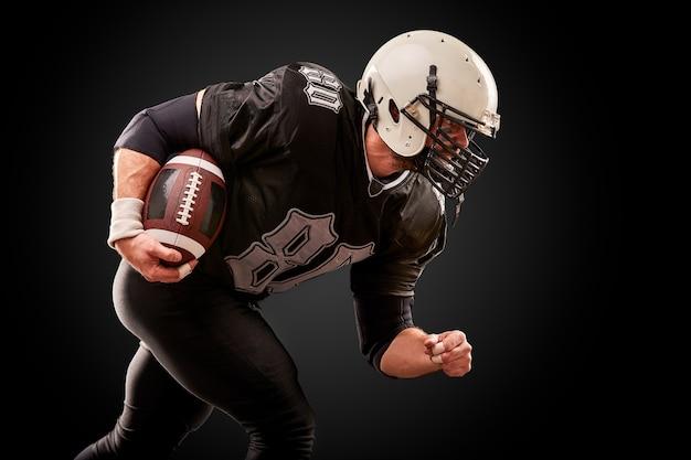 De amerikaanse voetballer in donker uniform met de bal treft voorbereidingen om op een zwarte achtergrond aan te vallen. Premium Foto