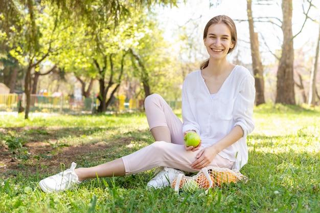 De appelzitting van de vrouwenholding op gras Gratis Foto
