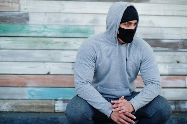 De arabische mens van portretsporten in zwart medisch gezichtsmasker en hoodie tijdens coronavirusquarantaine. Premium Foto