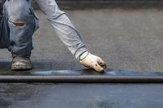 De arbeider die van azië teerfolie op het dak van de bouw installeert. Premium Foto