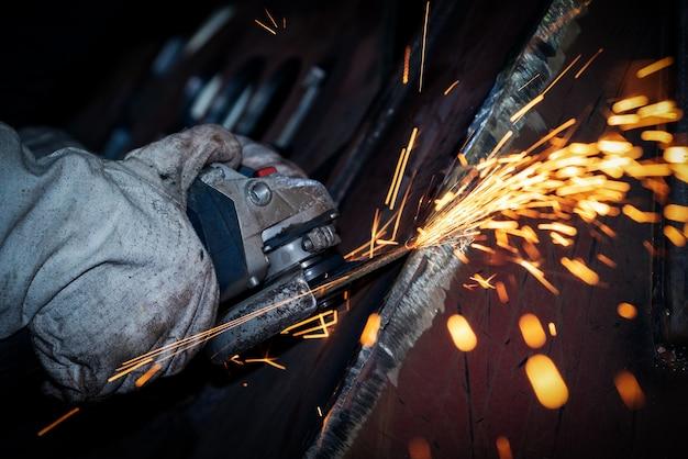 De arbeider slijpt metaal met een haakse slijper Premium Foto