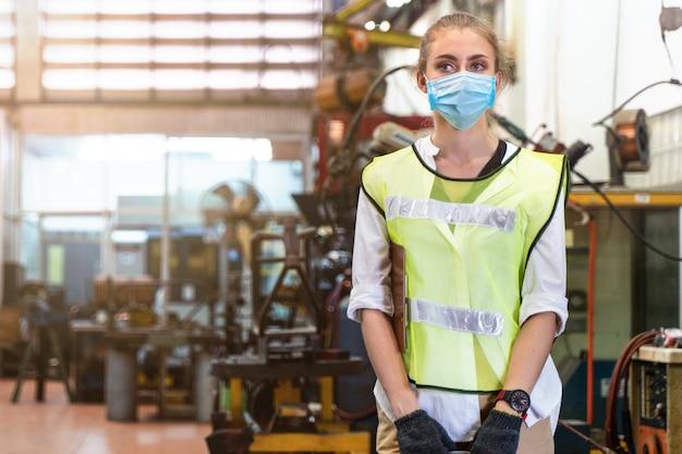 De arbeidersvrouw van de ziektevervaardiging met het gezichtstribunes van de maskerdekking met de achtergrond van binnenfabriek. Premium Foto