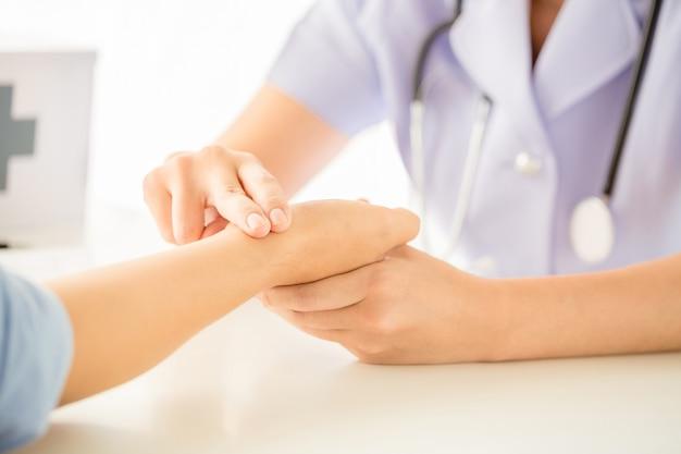 De arts controleert de pols van het geduld door vingers Gratis Foto