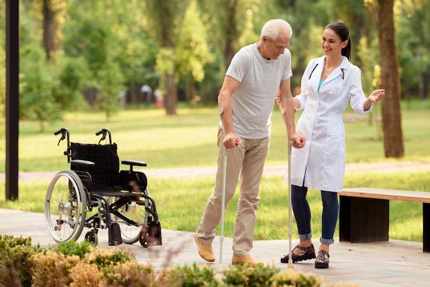 De arts helpt de patiënt op krukken te lopen. Premium Foto