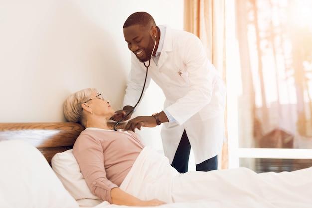 De arts onderzoekt een oudere patiënt in een verpleeghuis. Premium Foto