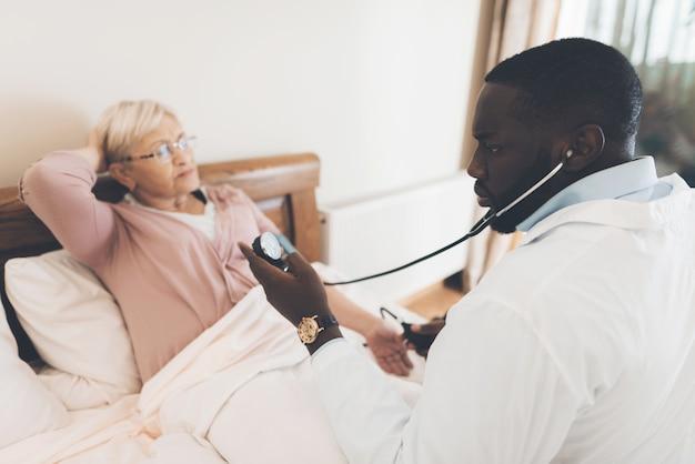De arts onderzoekt een oudere patiënt in een verpleeghuis Premium Foto