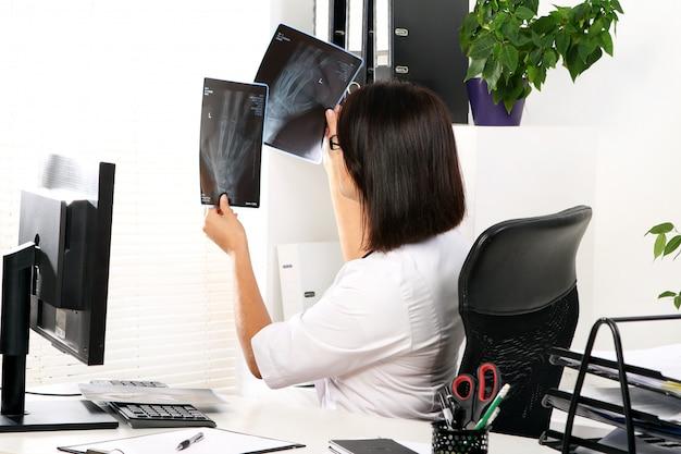 De arts van de vrouw bekijkt röntgenstraal van gebroken hand Gratis Foto