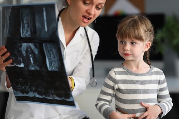 De arts van het kind kijkt x-ray beeld in het ziekenhuis Premium Foto