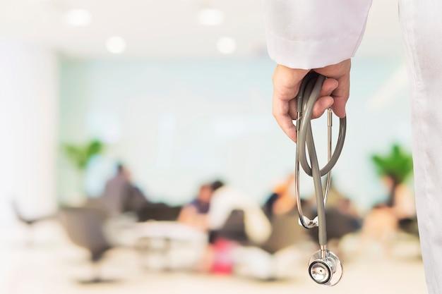 De arts zal zijn patiënt onderzoeken gebruikend zijn stethoscoop over zittingsmensen Gratis Foto