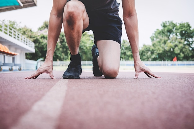 De atleet die van de geschiktheidsatleet aan het lopen op wegspoor voorbereidingen treffen, wellnessconcept van de trainingstraining Premium Foto
