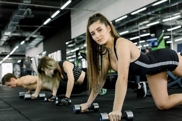 De atletenvrouw draaide zich uit op halters en kijkt in de camera. jonge man en twee vrouw training samen met halters in de sportschool Premium Foto