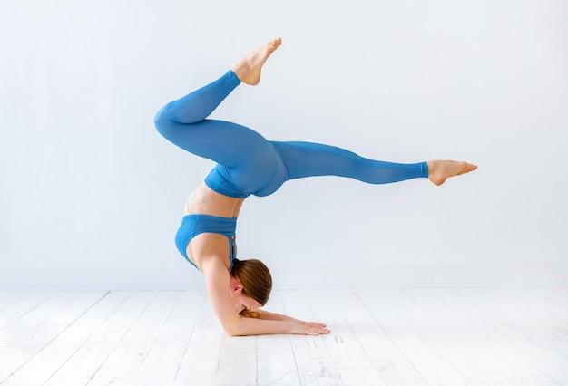 De atletische vrouw die een yoga van de elleboogtribune doen stelt Premium Foto