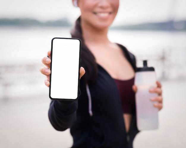 De atletische vrouw die van de close-up mobiele telefoon houdt Gratis Foto