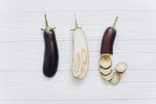 De aubergine wordt verscheurd op de witte houten achtergrond, hoogste mening. Premium Foto