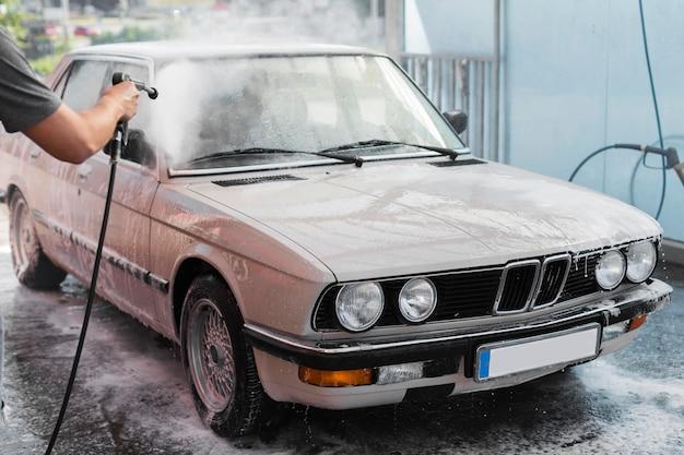De auto van de de handwas van de close-up met slang Premium Foto