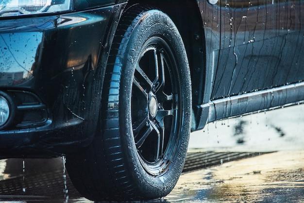 De auto wassen. een zwarte auto wassen bij een wasstraat. schone auto Premium Foto