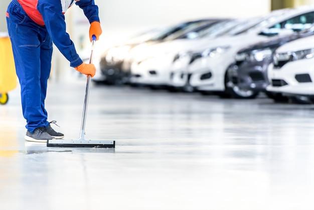 De automonteur reinigt met een dweil water uit de epoxyvloer. in het autoservice reparatiecentrum Premium Foto