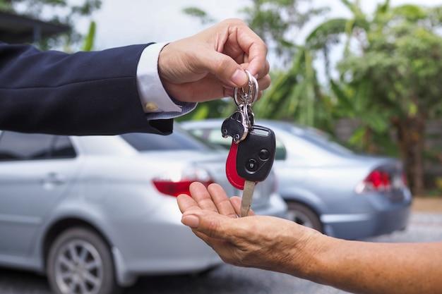 De autoverkoper stuurde de sleutels naar de nieuwe autobezitter. koop en verkoop huurconcept Premium Foto