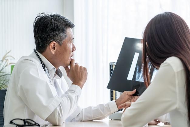 De aziatische arts en de patiënt bespreken Premium Foto