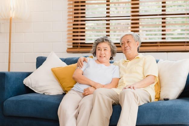 De aziatische bejaarde paar het letten op televisie in woonkamer thuis, zoete paar geniet liefde van ogenblik terwijl het liggen op de bank wanneer ontspannen thuis. Gratis Foto