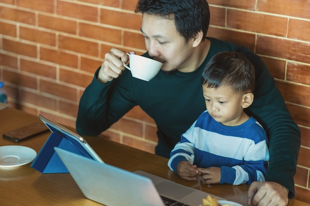 De aziatische enige papa met zoon kijkt het beeldverhaal via technologielaptop en het drinken koffie Premium Foto