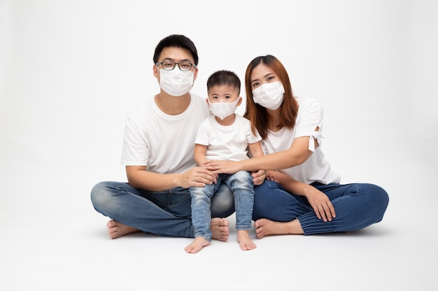 De aziatische familie die beschermend medisch masker dragen voor verhindert virus wuhan covid-19 en samen zittend op vloer geïsoleerde witte muur. familiebescherming tegen verontreinigd luchtconcept Premium Foto