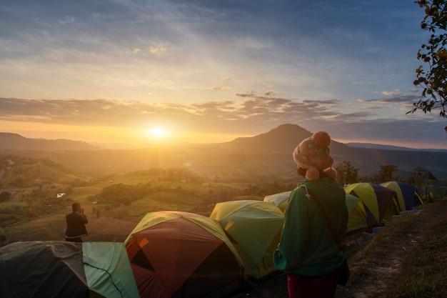 De aziatische gelukkige vrouw en de mening ontspannen tijdens dramatische zonsopgang nevelige ochtend, concept openlucht het kamperen avontuur Premium Foto