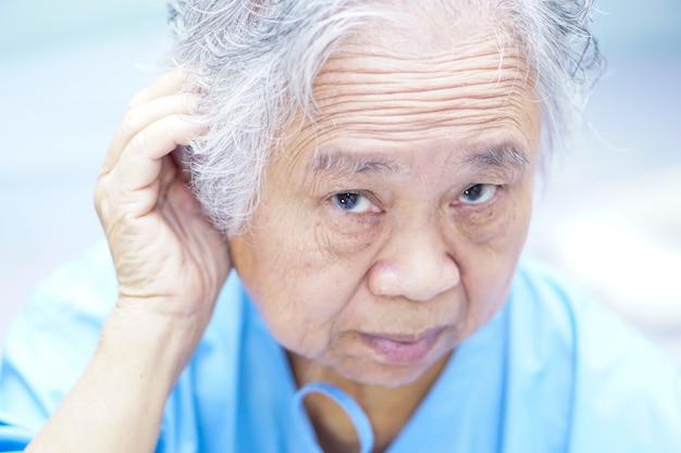 De aziatische hogere of bejaarde oude vrouw van de damevrouw probeert om oor, hard van hoorzitting te luisteren. Premium Foto