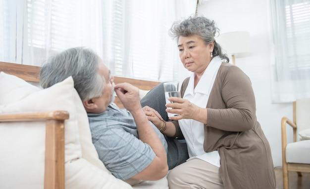 De aziatische hogere vrouw zorgt na geeft glas water aan de oudere man die geneesmiddelen en drinkwater nemen terwijl thuis lig op laag Premium Foto