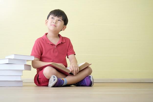 De aziatische jongen dagdroomt terwijl het houden van boek en vele boeken die aan kant worden geplaatst. Premium Foto