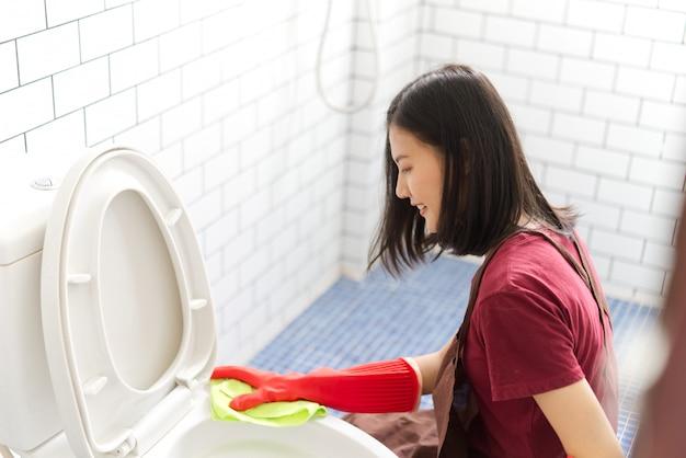De aziatische kom van het meisjes schoonmakende toilet door toilet te gebruiken veeg af. Premium Foto