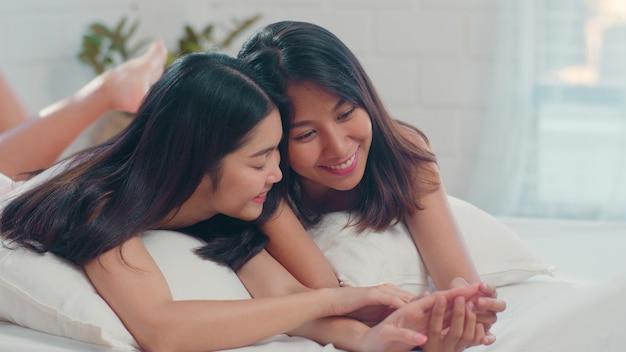 De aziatische lesbische lgbtq-vrouwen koppelen thuis kus en omhelzing op bed. Gratis Foto