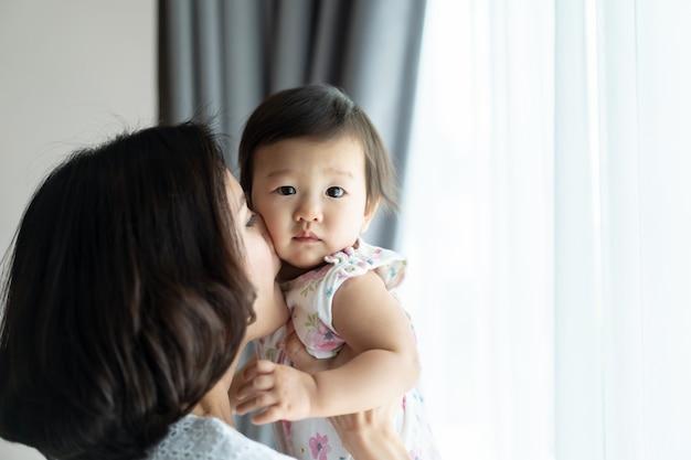 De aziatische mooie baby van de vrouwenholding en thuis het kussen van de jong geitjewang in ruimte. Premium Foto