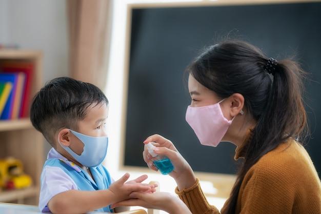 De aziatische nevel van het leraarsgebruik aan handen van haar student Premium Foto