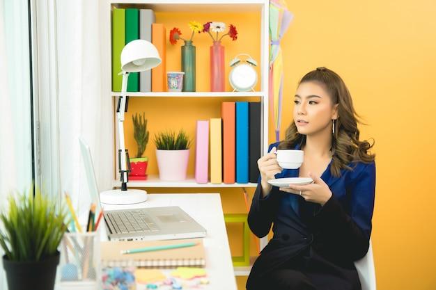 De aziatische onderneemster neemt een koffiepauze na het werken bij laptop computer aan bureau Gratis Foto