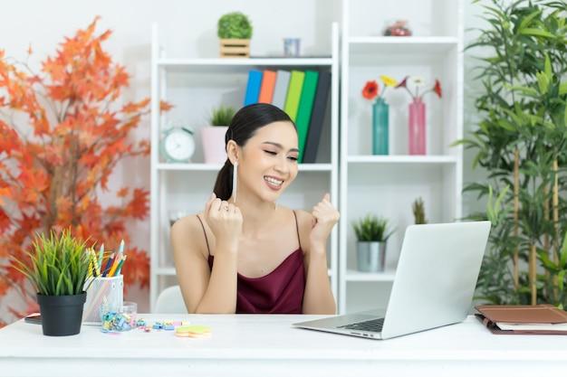 De aziatische onderneemster neemt een koffiepauze na het werken bij laptop computer op bureau Gratis Foto