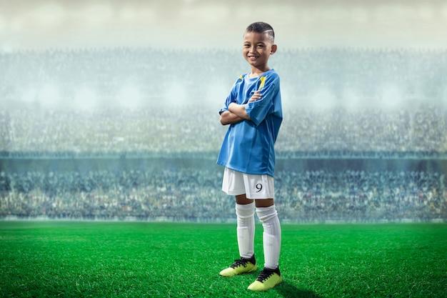 De aziatische speler van voetbaljonge geitjes in blauwe jersey die en zich aan camera in het stadion bevinden stellen Premium Foto
