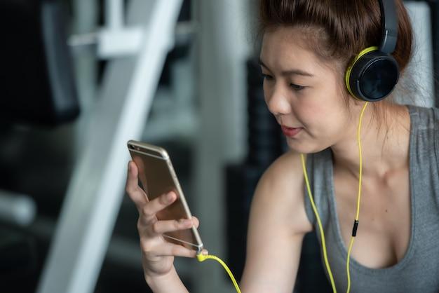 De aziatische sportvrouw die met oortelefoons aan muziek luisteren voor ontspant na harde trainingoefening in sportgymnastiek. Premium Foto