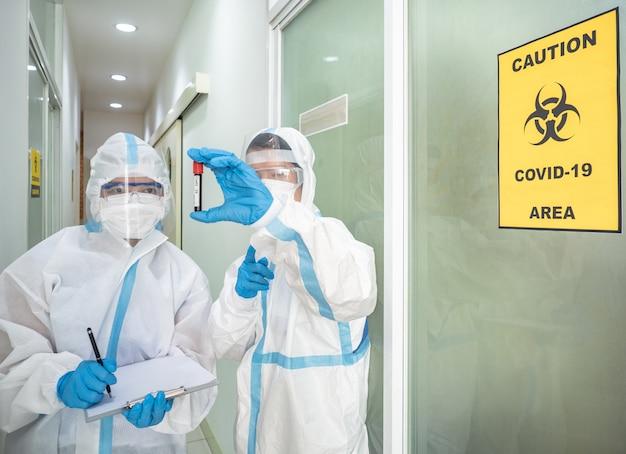 De aziatische vrouw arts in persoonlijk beschermend kostuum met masker schrijft op de quarantainepatiëntgrafiek, houdt bloedmonster voor onderzoek coronavirus met covid-19 gebieds alert teken. Premium Foto