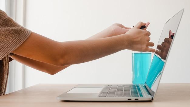 De aziatische vrouw die de hand van het het ontsmettingsmiddelwas van het alcoholgel gebruiken vóór het werk aan laptop voor beschermt coronavirus. vrouw duwt alcohol om schoon te maken voor hygiëne bij sociale afstand thuisblijven en zelfquarantainetijd. Gratis Foto