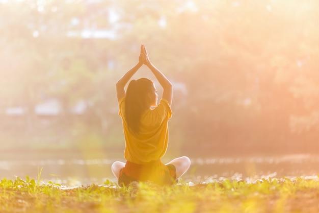De aziatische vrouw het praktizeren yogastrijder stelt Premium Foto