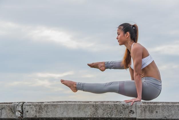 De aziatische vrouw in yoga stelt bovenop muur. Premium Foto