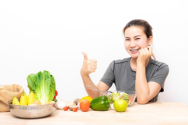 De aziatische vrouw van haapy met tandsteunen die duim tonen terwijl het eten van saladegroente op wit Premium Foto