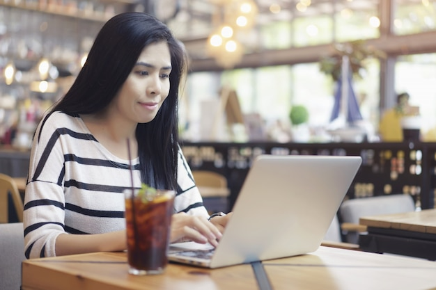 De aziatische vrouwen die computerlaptop gebruiken werken nieuwe projectzitting alleen bij koffie. Premium Foto