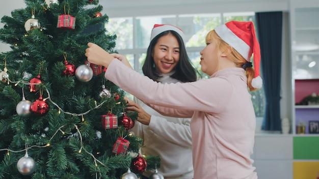 De aziatische vrouwenvrienden verfraaien kerstboom bij kerstmisfestival. het vrouwelijke tiener gelukkige glimlachen viert samen de vakantie van de kerstmiswinter samen in woonkamer thuis. Gratis Foto